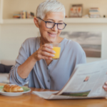 woman drinking juice reading newspaper at breakfast