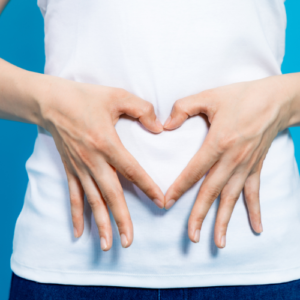 Woman holding a heart sign with hands at her stomach